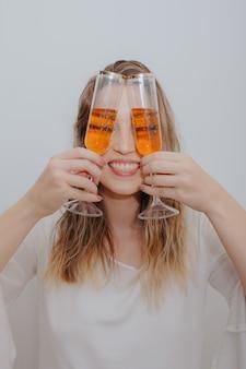 Młoda kobieta w białej sukni i dwie szklanki wina musującego w rękach przed jej twarzą