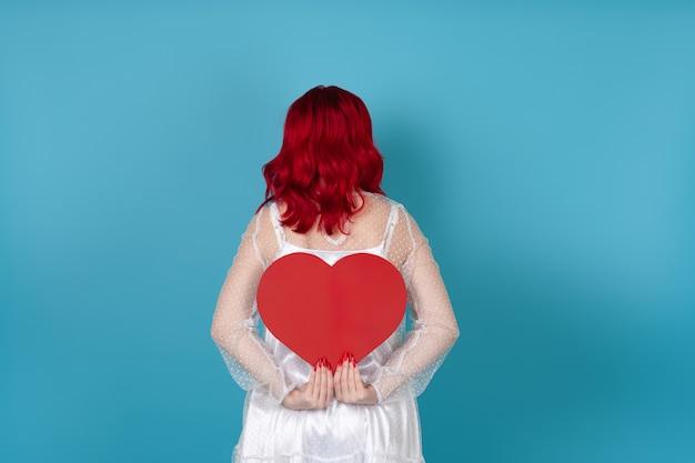 Młoda kobieta w białej sukni i rudych włosach trzyma za plecami duże czerwone papierowe serce