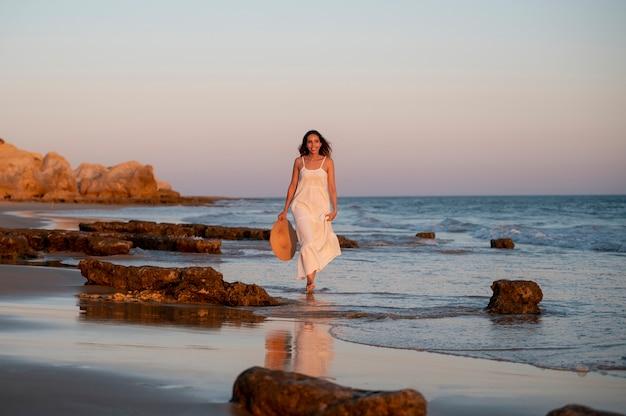 Młoda kobieta w białej sukni nad morzem