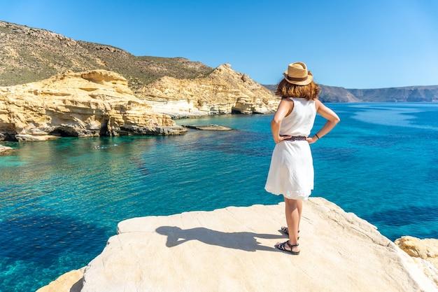 Młoda kobieta w białej sukni patrząca na morze w rodalquilar w cabo de gata w piękny letni dzień, almería