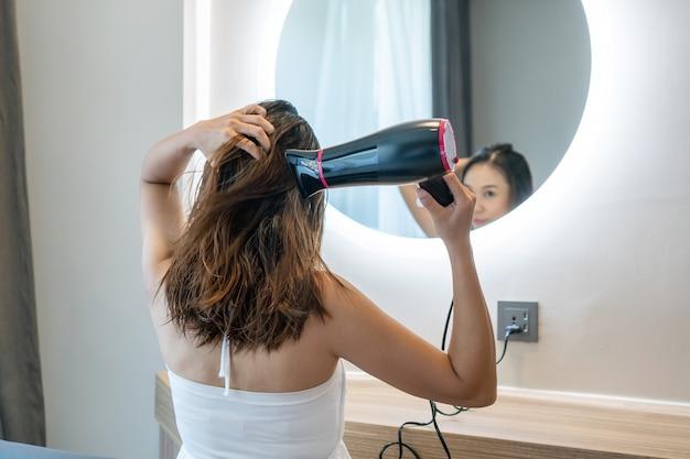 Młoda kobieta w białej sukni siedzi przed lustrem w pokoju hotelowym i wysuszyć mokre włosy po umyciu