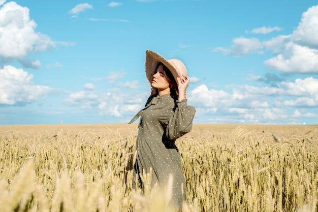 Młoda kobieta w białej sukni, słomkowym kapeluszu, kwiatowym polu, uszy chleba. piękna dziewczyna korzystających z pola kwiatów, relaks na świeżym powietrzu, koncepcja wolności harmonii.