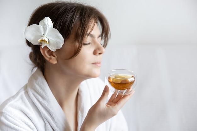 Młoda kobieta w białej szacie z kwiatem orchidei we włosach cieszy się herbatą, koncepcją zabiegów spa i relaksu.