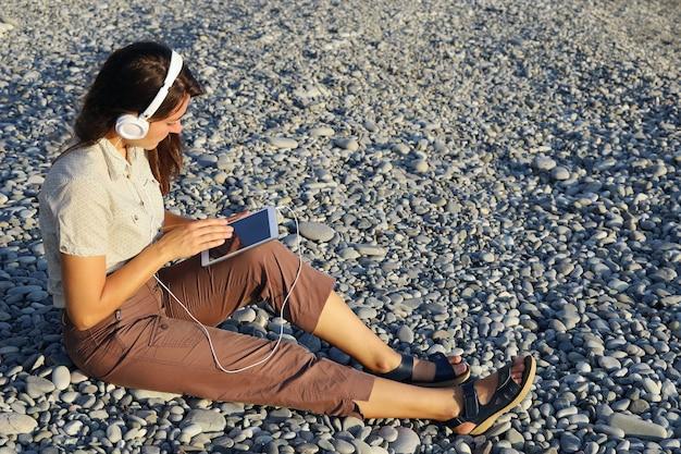 Młoda kobieta w białych słuchawkach trzyma tablet w dłoniach