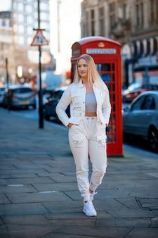 Młoda kobieta w białym kostiumie spaceruje po mieście