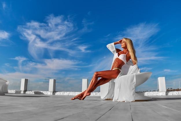 Młoda kobieta w białym pareo na tarasie i błękitne niebo na tle