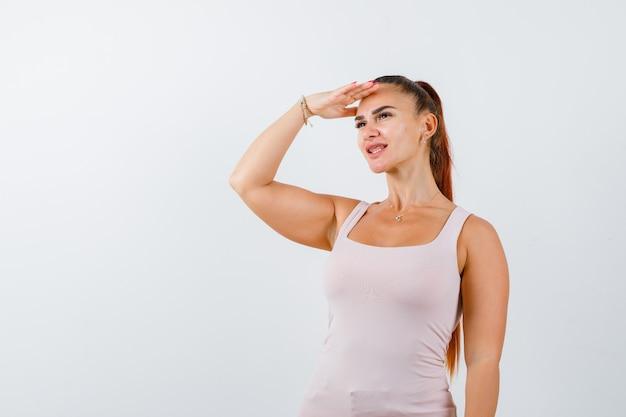 Młoda kobieta w białym podkoszulku bez rękawów, trzymając rękę na głowie, aby widzieć wyraźnie i ładnie wyglądający widok z przodu.