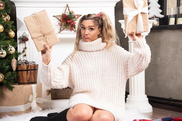 Młoda kobieta w białym swetrze przedstawiająca dwa pudełka prezentów świątecznych.