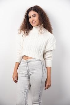 Młoda kobieta w białym swetrze stojąc na białej ścianie. wysokiej jakości zdjęcie