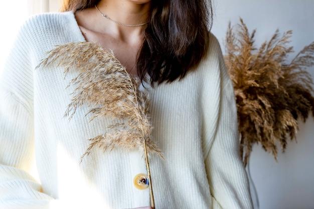 Młoda kobieta w białym swetrze trzyma trawę pampasową. bez portretu twarzy