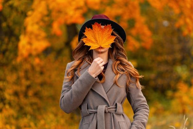 Młoda kobieta w białym swetrze z dzianiny trzyma w rękach pomarańczowo-złoty jesienny liść. kobieta z pięknym manicure'em leży na żółtych liściach w parku. skoncentruj się na kobiecych rękach z liści jesienią.