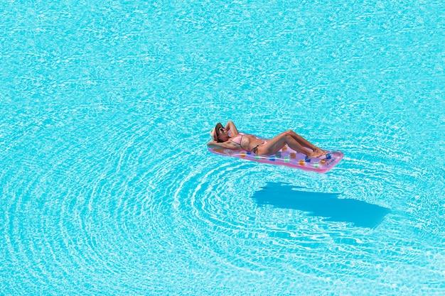 Młoda kobieta w bikini materac w dużym basenie