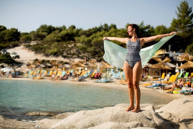 Młoda kobieta w bikini na skałach nad morzem