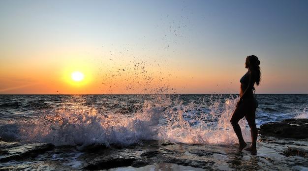 Młoda kobieta w bikini stojąc na skałach