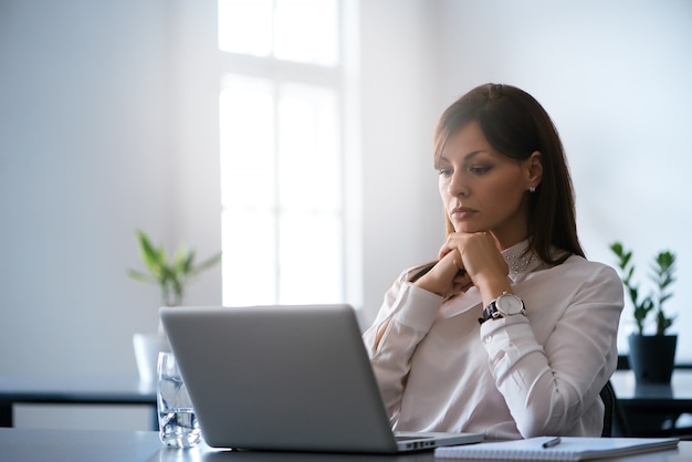 Młoda kobieta w biurze pracuje z laptopem