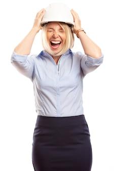 Młoda kobieta w biurze ubrania i kask budowy na głowie krzyczy. pionowy