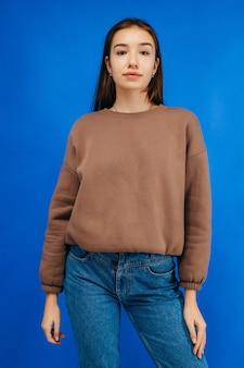 Młoda kobieta w bluza z kapturem pozowanie studio na niebieskim tle