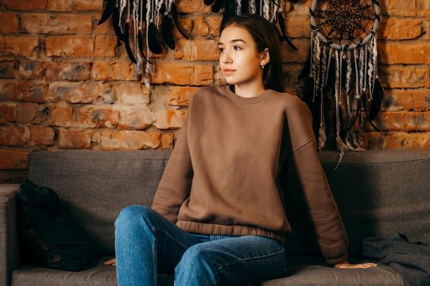 Młoda kobieta w bluza z kapturem pozowanie studio na tle ściany z cegły