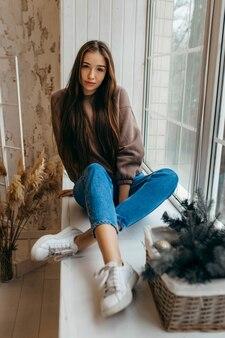Młoda kobieta w bluza z kapturem, pozowanie w studio, siedząc na parapecie