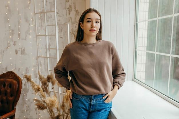 Młoda kobieta w bluza z kapturem pozowanie w studio