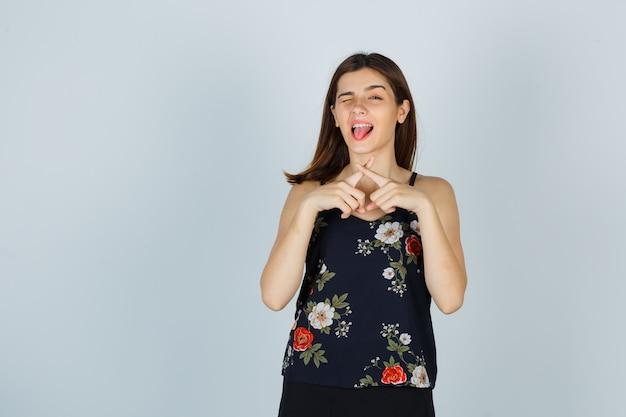 Młoda kobieta w bluzce pokazujący gest ciszy ze skrzyżowanymi palcami tworzącymi x, wystający język, mrugający i patrzący szczęśliwy, widok z przodu.