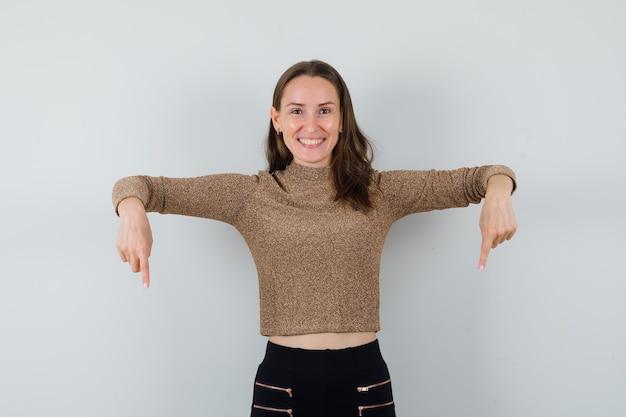 Młoda kobieta w bluzce, spódnica skierowana w dół i patrząc zadowolony, widok z przodu.