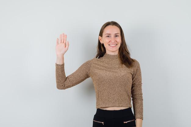 Młoda kobieta w bluzce, spódnicy macha ręką na pożegnanie i wygląda szczerze, widok z przodu.