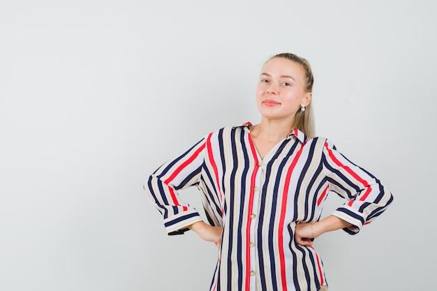 Młoda kobieta w bluzce w paski, kładąc obie ręce na biodrach i patrząc szczęśliwy