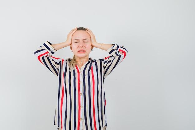 Młoda kobieta w bluzce w paski, obejmującej głowę obiema rękami i wyglądająca na zdezorientowaną