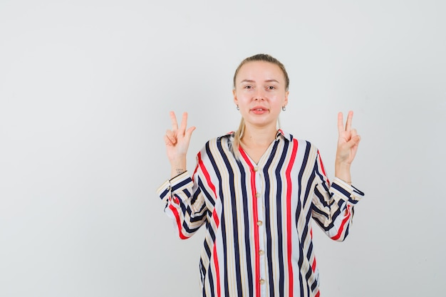 Młoda kobieta w bluzce w paski pokazując gest pokoju obiema rękami i patrząc optymistycznie