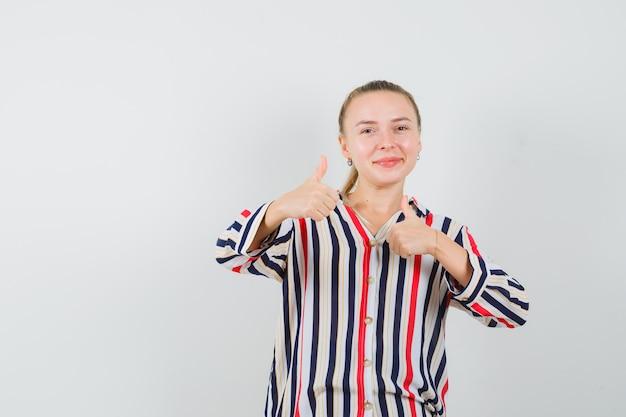 Młoda kobieta w bluzce w paski, pokazująca gesty obiema rękami i wyglądająca na szczęśliwą