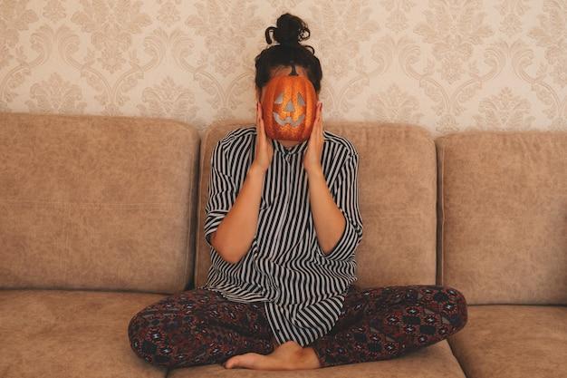 Młoda kobieta w bluzce w paski siedzi na sofie i trzyma dyni halloween w pobliżu jej twarzy