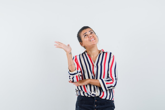 Młoda kobieta w bluzce w paski, stojąca w pozie słuchania i próbująca spojrzeć na coś powyżej i patrząc skupiona