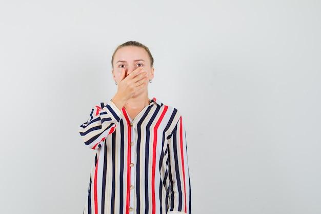 Młoda kobieta w bluzce w paski, zakrywająca usta obiema rękami i wyglądająca na zaskoczoną