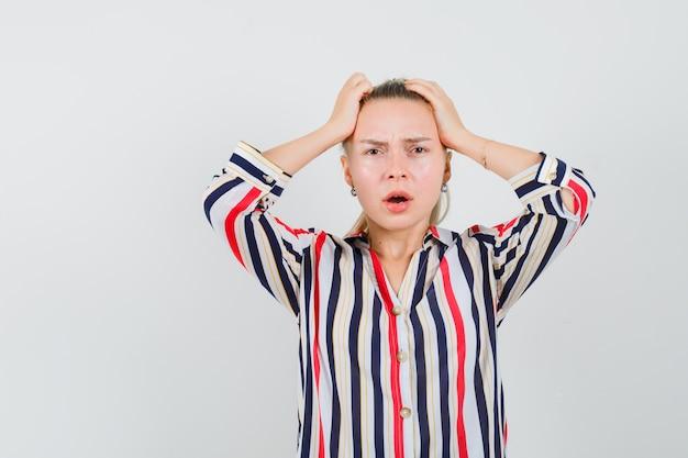Młoda kobieta w bluzce w paski, zakrywającej głowę obiema rękami i wyglądająca na zaskoczoną