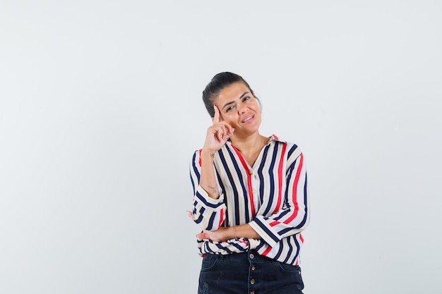 Młoda kobieta w bluzkę w paski, opierając policzek pod ręką i stojąc w pozie słuchania i patrząc optymistycznie
