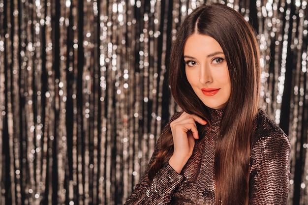 Młoda kobieta w błyszczącej kurtce na srebrnej ścianie świecidełka