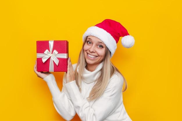 Młoda kobieta w bożonarodzeniowym białym swetrze i czapce mikołaja demonstruje pudełko z białą kokardką