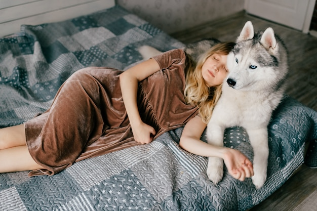 Młoda kobieta w brązowej sukni, leżąc na łóżku w domu z husky szczeniaka.