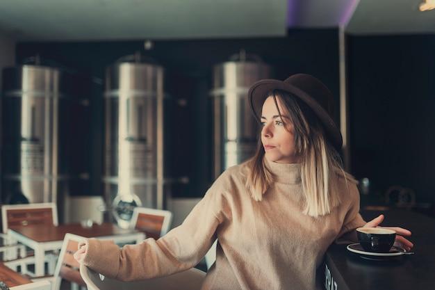 Młoda kobieta w brązowy sweter i brązowy kapelusz czeka na kogoś w kawiarni, trzymając jego filiżankę kawy
