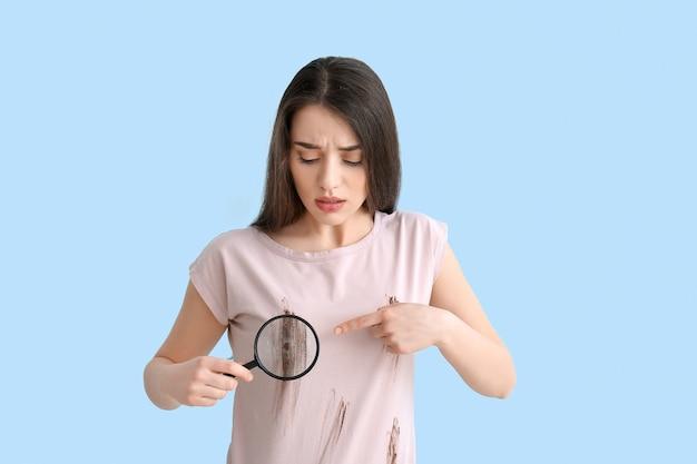 Młoda kobieta w brudnych ubraniach i z lupą na kolorowym tle