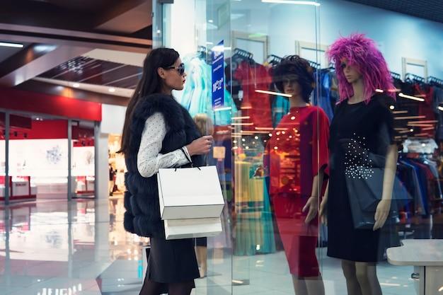 Młoda kobieta w centrum handlowym, stojąc w pobliżu witryny sklepowej i patrząc na dwa manekiny w sukienkach i perukach. modna atrakcyjna dziewczyna robi zakupy w centrum handlowym. pani w okularach szuka stroju.