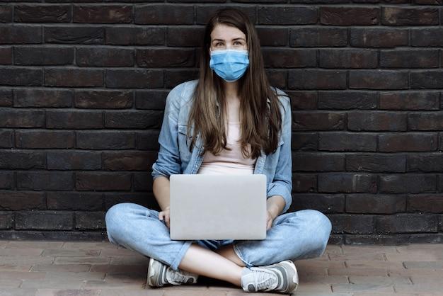 Młoda kobieta w chirurgicznej masce medycznej na twarzy chroniącej przed rozprzestrzenianiem się pandemicznego koronawirusa