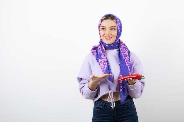 Młoda kobieta w chustce trzyma czerwoną paprykę.