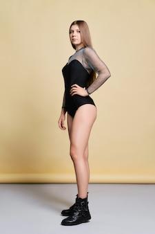 Młoda kobieta w ciasnym body i szorstkich butach pozowanie w studio na bladożółtym