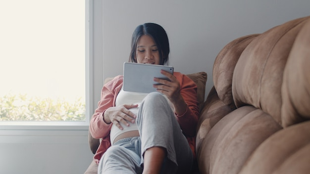 Młoda kobieta w ciąży azji za pomocą tabletu wyszukiwania informacji o ciąży. mama czuje się szczęśliwy, uśmiechnięty pozytywnie i spokojnie, podczas gdy dbać o swoje dziecko leżące na kanapie w salonie w domu.