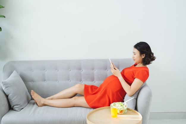 Młoda kobieta w ciąży korzysta z telefonu leżąc na kanapie, jedząc sałatkę, pijąc sok pomarańczowy.