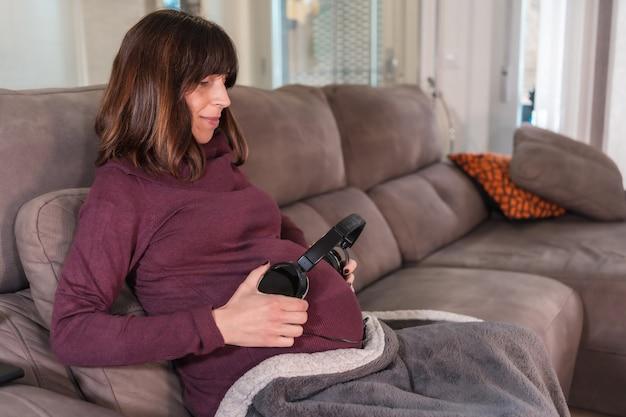 Młoda kobieta w ciąży łączy się z dzieckiem wkładając muzykę przez słuchawki, w dobrobycie jej domu