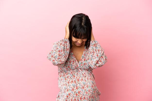 Młoda kobieta w ciąży na odosobnionym różowym tle sfrustrowana i zakrywająca uszy