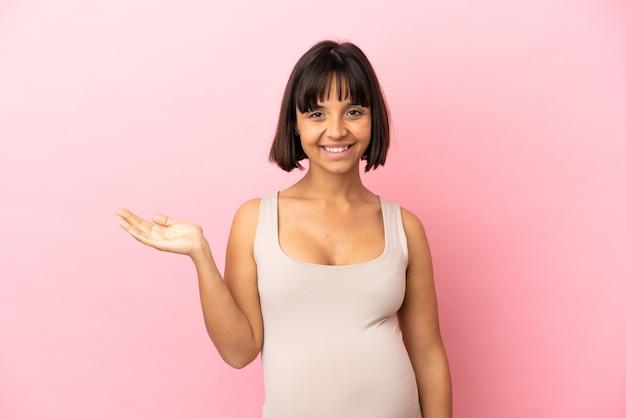 Młoda kobieta w ciąży na odosobnionym różowym tle trzyma wyimaginowaną copyspace na dłoni, aby wstawić reklamę